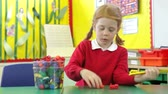sentar se : Female Pupil Counting Plastic Toys At Desk