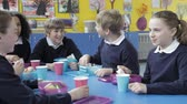 dolly : Schoolchildren Sitting At Table Eating Packed Lunch