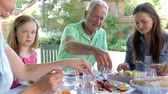 três : Multi-Generation Family Sitting Outdoors Around Table Eating Stock Footage
