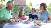 grandparents : Grandparents And Grandchildren Sitting Outdoors Eating