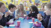 sentar se : Schoolchildren Sitting Eating Packed Lunch With Teacher Stock Footage