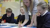 quatro pessoas : Pupils Working At Table With Teacher Helping Them