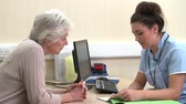gp : Nurse Discussing Test Results With Senior Female Patient