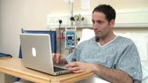 cama : Male Patient Using Laptop In Hospital Bed