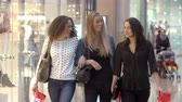 decisão : Three Female Friends Shopping In Mall Together