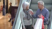 escada rolante : Happy Senior Couple On Escalator In Shopping Mall Stock Footage