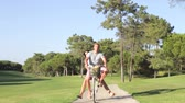велосипед : Couple Sharing Bike On Cycle Ride In Park Стоковые видеозаписи