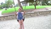 se divertindo : Slow Motion Sequence Of Girl On Swing In Playground Waving Stock Footage