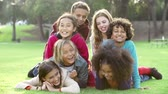 se divertindo : Group Of Children Lying On Grass Together In Park Stock Footage