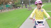 cyklus : Young Girl Riding Bike In Park Looking At Camera Dostupné videozáznamy