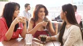 grupo de pessoas : Three Female Friends Enjoying Drink At Outdoor Rooftop Bar