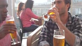 etniczne : Three Male Friends Enjoying Drink At Outdoor Rooftop Bar Wideo
