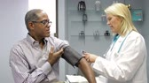 monitoração : Doctor Checking Male Patients Blood Pressure