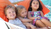 se divertindo : Three Children Relaxing In Garden Hammock Together Stock Footage