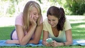 mensagem : Two Teenage Girls Lying In Garden Reading Text Message