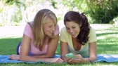 reading : Two Teenage Girls Lying In Garden Reading Text Message