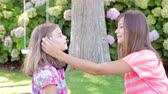 подросток : Teenage Girl Talking To Younger Sister In Garden