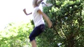 desfrutando : Young Girl Jumping On Trampoline In Garden Stock Footage