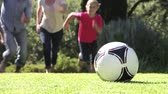 pontapé : Family Running To Kick Football In Garden
