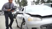 афроамериканца : Loss Adjuster Inspecting Car Wreck Using Digital Tablet