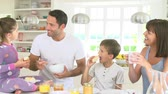 musli : Family Eating Breakfast In Kitchen Together