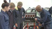 estudantes : Teacher In Car Mechanic Class Demonstrating How Engine Works Stock Footage