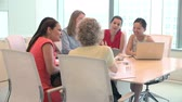 americano africano : Group Of Businesswomen Meeting Around Desk In Office