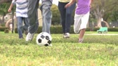 выстрел : Slow Motion Shot Of Hispanic Family Playing Soccer Together