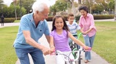 dzieci : Grandparents Teaching Grandchildren To Ride Bikes In Park