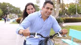 cyklus : Young Hispanic Couple Riding Bike In Park Dostupné videozáznamy