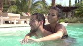 se divertindo : Slow Motion Shot Of Young Couple Relaxing In Swimming Pool Stock Footage