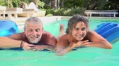 traje : Mature Couple Relaxing On Airbed In Swimming Pool Stock Footage