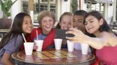 americano africano : Group Of Children In Café Taking Selfie On Mobile Phone Stock Footage
