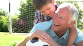 velho : Slow Motion Shot Of Grandfather And Grandson With Football