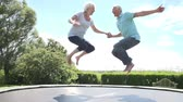 jouïssance : Couple senior Bouncing Sur Trampoline In Slow Motion