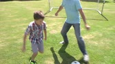 pontapé : Grandfather And Grandson Playing Football In Garden At Home