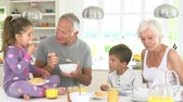 four people : Grandparents With Grandchildren Eating Breakfast In Kitchen