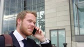 building : Young man on the phone walking to entrance of a modern business building Stock Footage