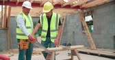 building : Carpenter With Male Apprentice Cutting Wood On Building Site