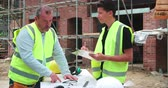 internar : Builder On Site Discussing Work With Male Apprentice Vídeos
