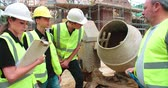 смешивание : Builder Using Cement Mixer On Building Site With Apprentices