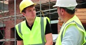 internar : Builder On Building Site Discussing Work With Apprentice