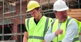 site : Builder On Building Site Discussing Work With Apprentice