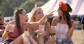 relaxation : Three female friends sitting on grass at a music festival