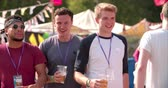 pessoa : Three male friends walking at a music festival, slow motion
