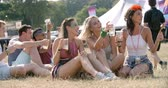 passar : Friends sitting on grass watching a gig at a music festival Vídeos