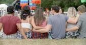 scena : Friends sit on grass talking at a music festival, back view Wideo