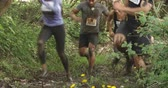 concorrentes : Assault course competitors running through forest, low angle