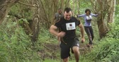 concorrentes : Competitors running through a forest at an endurance event Stock Footage