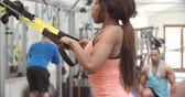 resistência : Young woman doing bodyweight workout in a busy gym